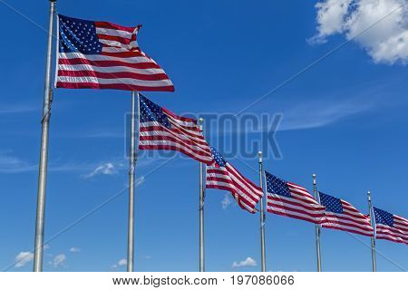 Row of flags against the blue sky wave in the wind.
