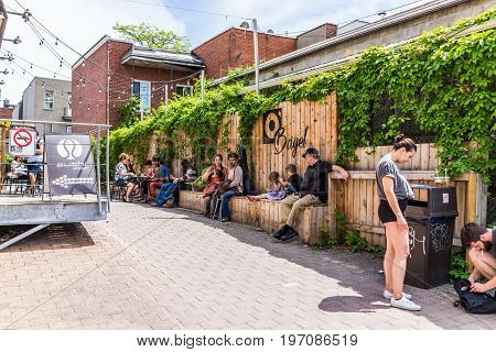 Montreal, Canada - May 28, 2017: People Sitting Outside Restaurants Near Jean-talon Farmers With Bag