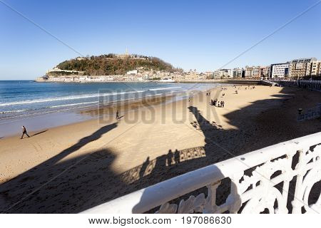 DONOSTI, SPAIN-DECEMBER 21 2014: On sunny days the people of Donosti take the opportunity to stroll along La Concha Beach on 21 December, 2014