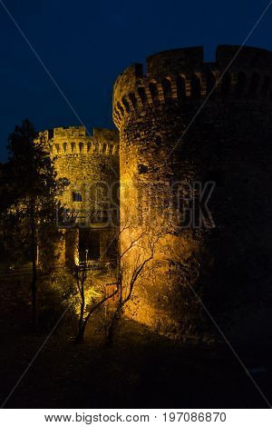 Kalemegdan fortress gate with towers and a wooden bridge at night in Belgrade, Serbia