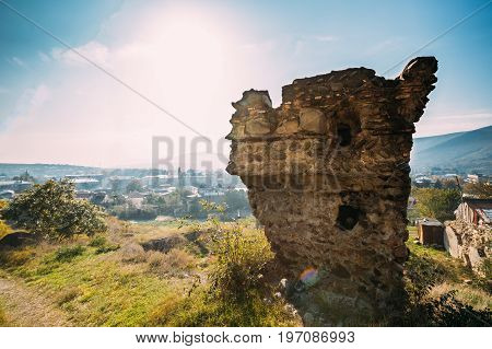 Gori, Shida Kartli Region, Georgia. Stone Wall Remains Of Gori Fortress. Goris Tsikhe Is A Medieval Citadel Standing Above The City Of Gori On A Rocky Hill. Sunny Autumn Day With Blue Sky.