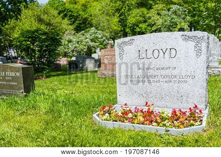 Montreal, Canada - May 28, 2017: Cemetery On Mont Royal With Grave Tombstone Of Lloyd Sign And Flowe