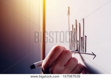 Businessman drawing a graph chart on whiteboard in the office during business results presentation