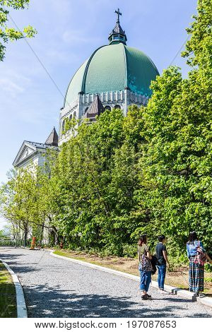 Montreal Canada - May 28 2017: St Joseph's Oratory on Mont Royal with dome during bright sunny day in Quebec region city with people walking on trail path