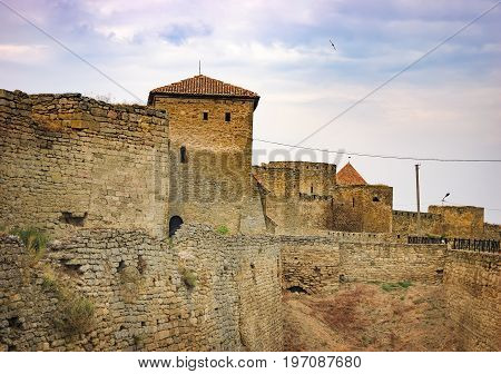 Walls arched windows and the pointed conical roof of Fortress Akkerman in Bilhorod-Dnistrovskyi, Ukraine. Around the castle is drained the moat which had previously been water.