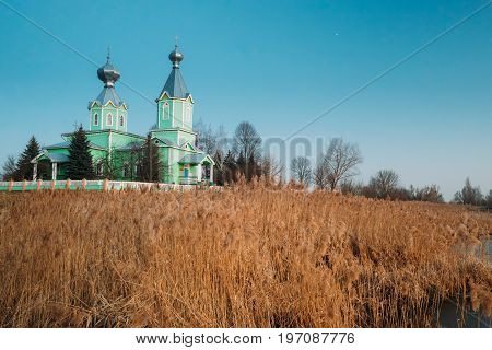 Old Wooden Orthodox Church Of The Holy Trinity In Village Old Krupets, Dobrush District, Gomel Region, Belarus. Landscape With Old Church And Spring Or Autumn Thickets of Bulrush At Evening.