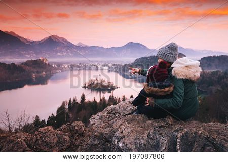 Family travel Slovenia Europe. Mother with son looking on sunset on Bled Lake. Winter landscape. Top view on Island with Catholic Church in Bled Lake with Castle and Alps Mountains in Background.