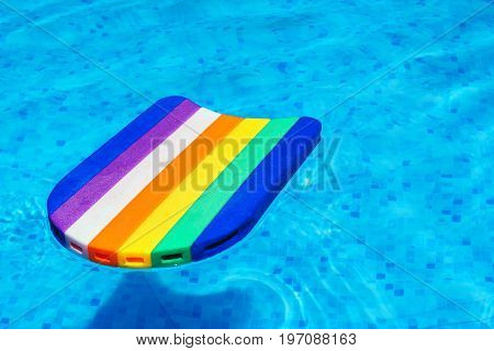 Rainbow pattern styrofoam swimming board or baseboard floating in swimming pool water summertime vacation recreational activity object in the poolside