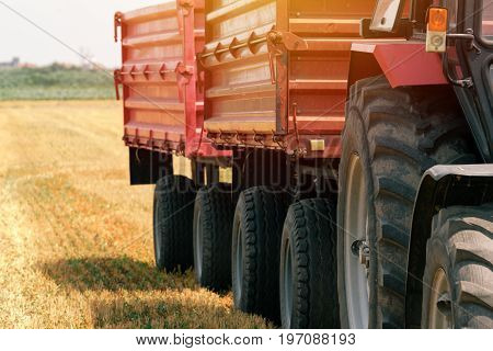 Tractor with wagon trailer in field on bright sunny day