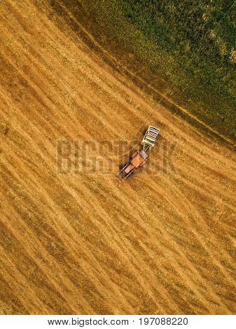 Aerial view of tractor making hay bale rolls in field after wheat harvest drone pov