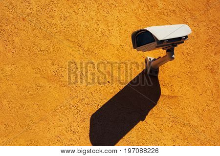 Security camera on yellow wall modern surveillance technology on building facade with shadow