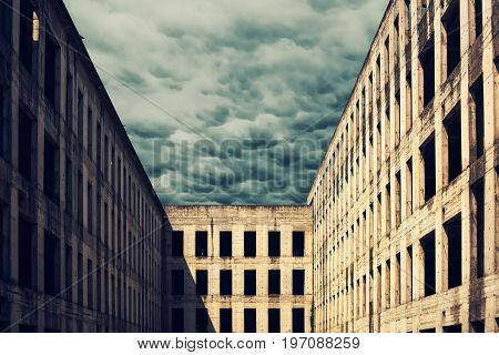 Unfinished abandoned concrete building facade with dark stormy clouds in the background