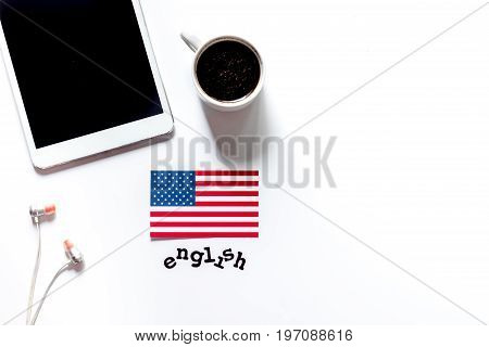 Self-education. Learning english online. Headphones and tablet PC on table background top view.