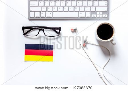 Self-education. Learning languages online. Headphones and keyboard on white table background top view.