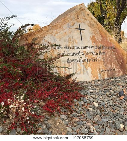 Psalm 78:16 etched into a large stone of various browns with red and green leaves from a bush on a fall day in Central Oregon.