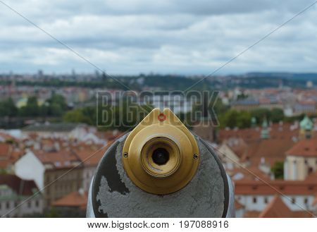 Detail on city telescope in focus in foreground while view on the city is a blurred in the background