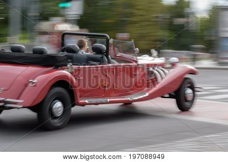 Old red speeding car riding on a street. Speed is symbolized by a blur. Therefore there is blurry background.