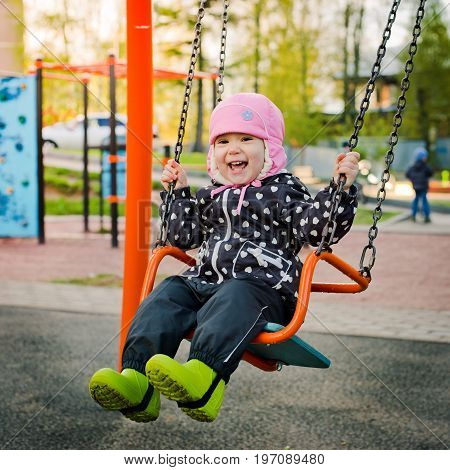 Child on a swing in spring or autumn