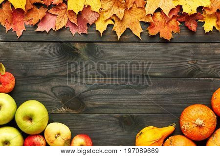 Autumn leaves, apples and pumpkins over old wooden background with copy space