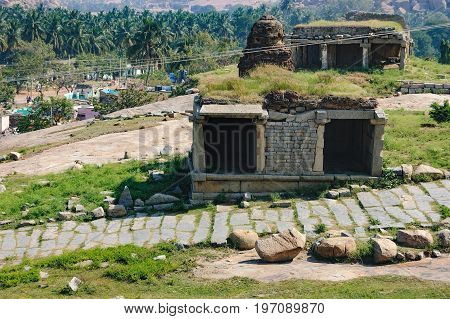 View of ancient ruins on Hemakuta hill in Hampi, Karnataka, India. Landscape with unique mountain formation Hampi Village in the distance tropical nature and the road along temple.