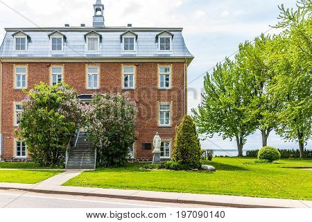 Champlain Canada - May 29 2017: Brick church in small town on Chemin du Roy with Saint Lawrence river