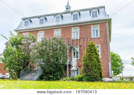Champlain, Canada - May 29, 2017: Brick Church In Small Town On Chemin Du Roy With Field Of Yellow D