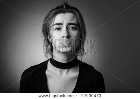 sad girl with plaster on her mouth looking at camera at gray background, monochrome