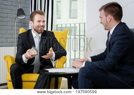 Real estate agent discussing with customer. Blueprints and house model on table.