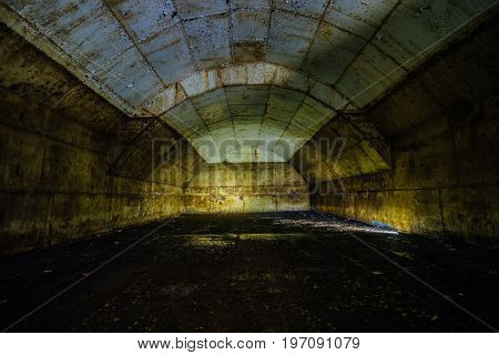 Inside big rusty underground abandoned fuel tank for refueling diesel submarines at repair factory