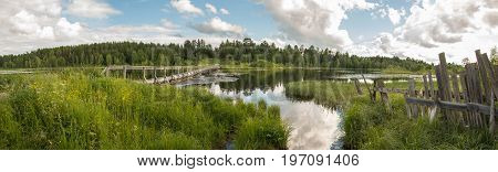 north Russian village Isady. Summer day Emca river old cottages on the shore old wooden bridge and clouds reflections