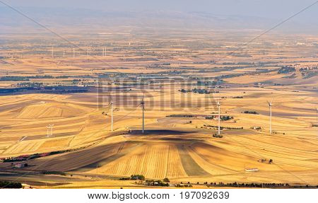 the yellow plain of the Tavoliere delle Puglie with wind turbines as seen from Monti Dauni hills in Gargano - Apulia - Italy
