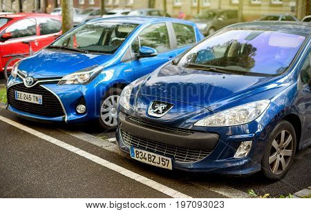 STRASBOURG FRANCE - MAY 30 2017: Peugeot 206 and Toyota hybrid car parked on a street near the bicycle lane