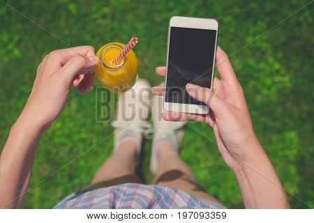 High angle view of female holding glass bottle of fresh orange juice and blank screen smartphone on field. Healthy lifestyle and technology concepts.