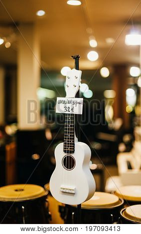 White Ukulele soprano guitare for sale in the windows of a music store in France