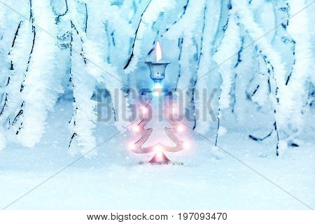 Christmas tree in a snowy forest. A metal candlestick in the form of a New Year's spruce. New Year's art image.