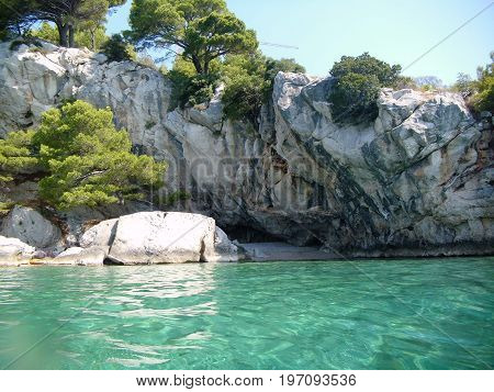 Seashore with turqoise water, grey rock and trees