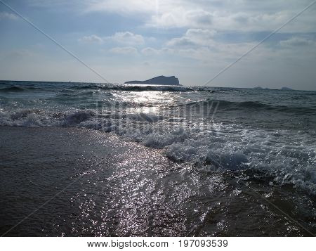 sea waves at the seashore with a rock isle