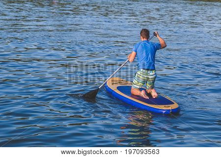 Young man stand up paddle surfing on board