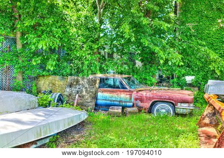 Junk car in grass hdr with vibrant colors in summer shed