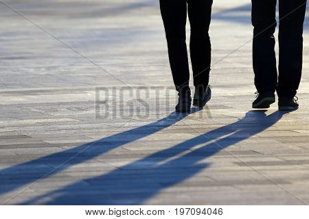 legs of two people coming together in the square