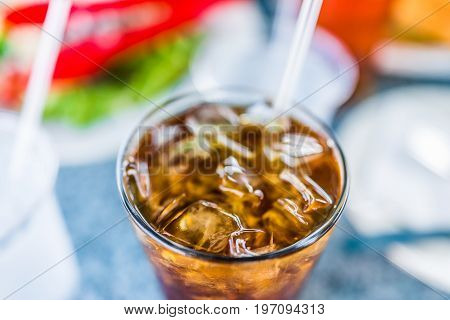 Macro Closeup Of Iced Tea Or Coke With Cubes Of Ice And Straw In Glass