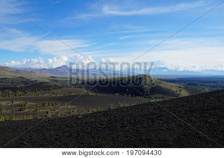 View over a black volcanic lava landscape from the Inferno Cone. A cinder cone rising above a landscape of black volcanic basalt rock and volcano domes from eruptions. Craters of the Moon.
