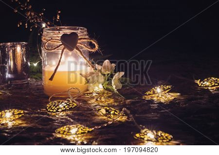 Romantic still life with candlelight, decorative garlands and flowers. Place for text, dark background.
