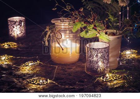 Romantic still life with candlelight, decorative garlands and flowers.
