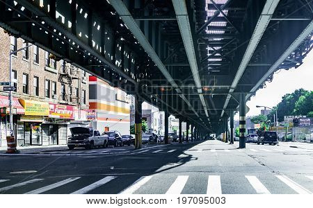 Bronx, Usa - June 11, 2017: Road And Street Under Subway Railroad With Restaurants And Shops With Si