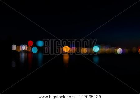 Bokeh of city night lights on water with reflection of cityscape or skyline of Baltimore Maryland