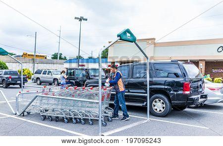 Burke USA - June 16 2017: Hmart shopping carts with man worker organzing them