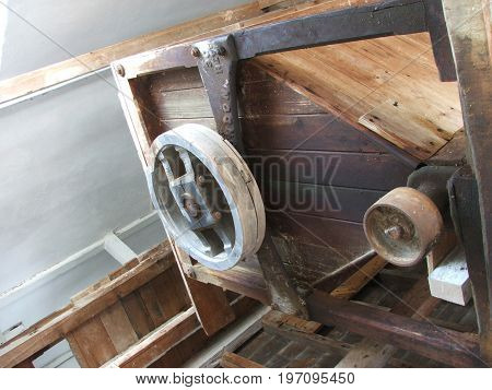 gears and pulleys in an old wooden watermill used for grinding flour