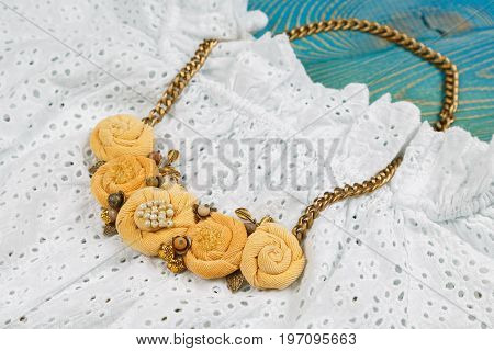 Peach-colored handicraft necklace lies on lace dress