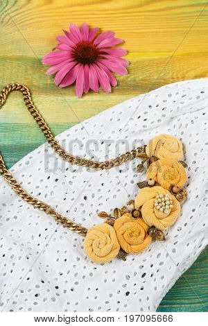 Handicraft necklace lies on the white lace dress background